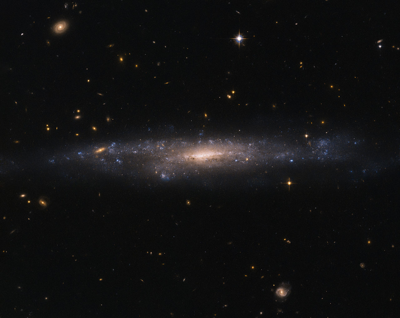 This striking NASA/ESA Hubble Space Telescope image captures the galaxy UGC 477, located just over 110 million light-years away in the constellation of Pisces (The Fish). UGC 477 is a low surface brightness (LSB) galaxy. First proposed in 1976 by Mike Disney, the existence of LSB galaxies was confirmed only in 1986 with the discovery of Malin 1. LSB galaxies like UGC 477 are more diffusely distributed than galaxies such as Andromeda and the Milky Way. With surface brightnesses up to 250 times fainter than the night sky, these galaxies can be incredibly difficult to detect.  Most of the matter present in LSB galaxies is in the form of hydrogen gas, rather than stars. Unlike the bulges of normal spiral galaxies, the centres of LSB galaxies do not contain large numbers of stars. Astronomers suspect that this is because LSB galaxies are mainly found in regions devoid of other galaxies, and have therefore experienced fewer galactic interactions and mergers capable of triggering high rates of star formation. LSB galaxies such as UGC 477 instead appear to be dominated by dark matter, making them excellent objects to study to further our understanding of this elusive substance. However, due to an underrepresentation in galactic surveys — caused by their characteristic low brightness — their importance has only been realised relatively recently.