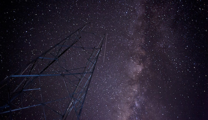 This long-exposure photograph shows a meteor trail (C) against the backdrop of the Milky Way galaxy as a mobile phone tower under construction is pictured in the foreground near Loikaw, Kayar state in Myanmar on October 11, 2014. AFP PHOTO / Ye Aung THU        (Photo credit should read Ye Aung Thu/AFP/Getty Images)